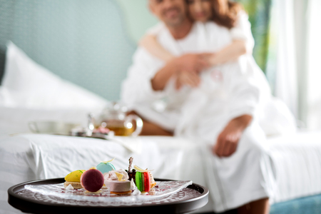 Selective focus of delicious dessert and couple sitting on the bed