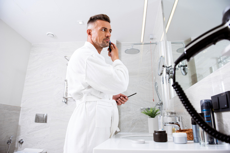Man in front of the mirror working at his hairstyle