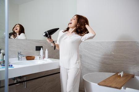 Femme positive avec un sèche-cheveux dans sa main chantant