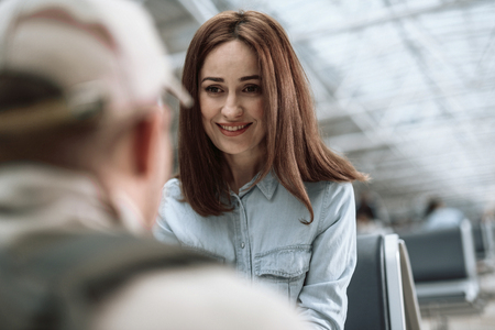 Cropped photo of happy woman smiling to her husband in waiting room Archivio Fotografico