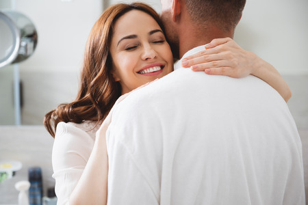 Man in bathrobe and pleased woman hugging him Stock Photo