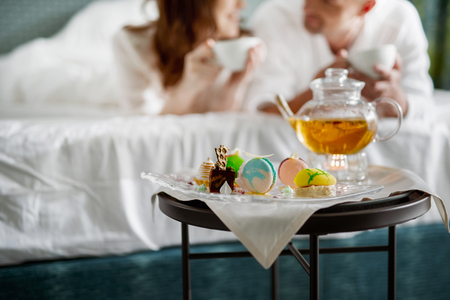 Bedside table with teapot and delicious desserts on it