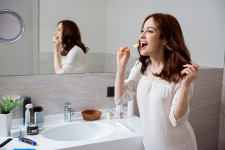 Aufgeregte Frau mit Zahnpasta auf ihrer Zahnbürste, die glücklich lächelt Standard-Bild