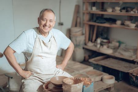Half length of happy handsome old potter working in potters studio