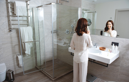 Modern bathroom with young woman cleaning her face pores
