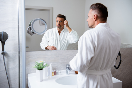 Handsome young man combing his hair in front of the mirror