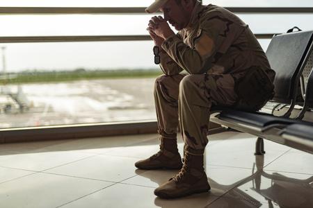 Niedriger Winkel des amerikanischen Soldaten in Tarnung, der drinnen betet Standard-Bild