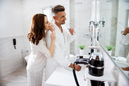 Loving couple smiling while doing morning hygiene procedure together