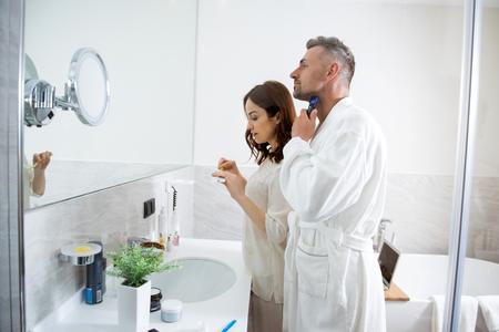 Woman brushing her teeth while smiling man shaving his beard Stock Photo
