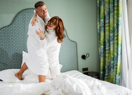 Positive couple dancing on the bed and looking happy
