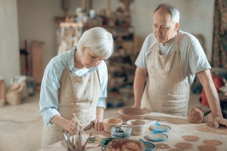 Waist up of old couple working in potters studio Stock fotó