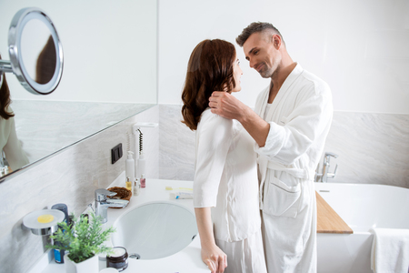 Man in bathrobe putting his hand on the shoulder of woman Stock Photo
