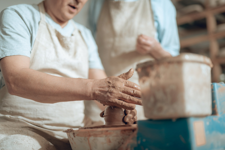 Low angle of male hands working with wet clay in potters studio Stock fotó