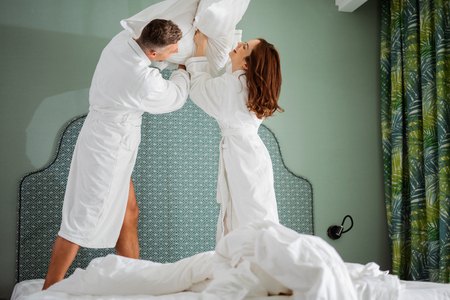 Active couple enjoying their pillow fight and smiling