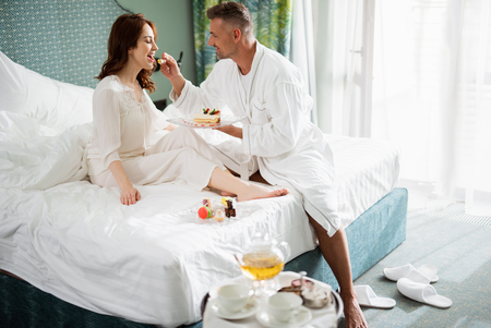 Man in the bathrobe feeding young lady with tasty cake Stock Photo