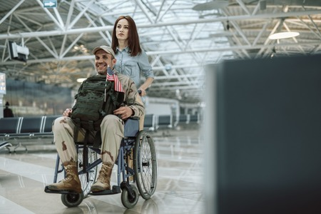 Wife carrying wheelchair and situating behind her husband in military uniform Stok Fotoğraf - 124538443
