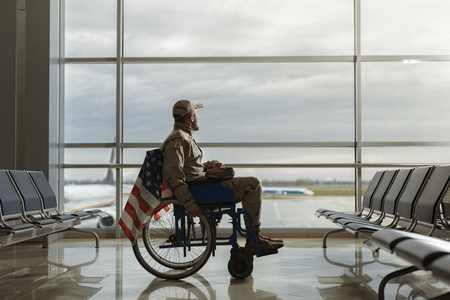 Side view of military man sitting in wheelchair