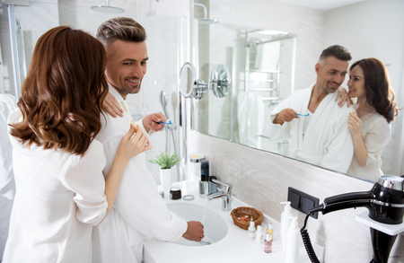 Loving couple in front of the mirror with toothbrushes in their hands