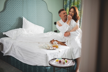 Positive romantic couple enjoying breakfast in bed and smiling Stock Photo