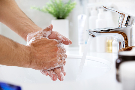 Man with soapy hands near the running water from the tap Stockfoto