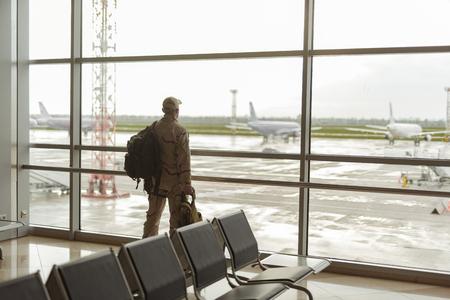 Photo recadrée d'un soldat américain en tenue de camouflage regardant la fenêtre
