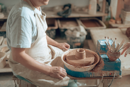 Cropped photo of mature craftsman sitting on chair in potters studio