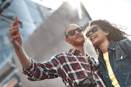 Cheerful young people are taking selfie outdoor Imagens