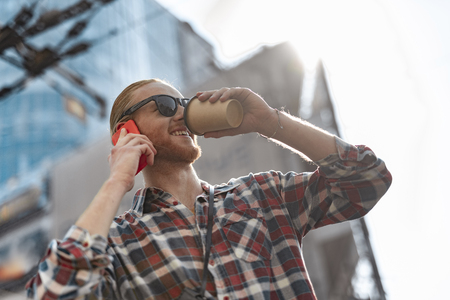 Jolly man is drinking coffee while making call outdoors Stock Photo