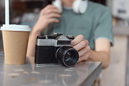 Male with retro camera and hot drink indoors Stockfoto