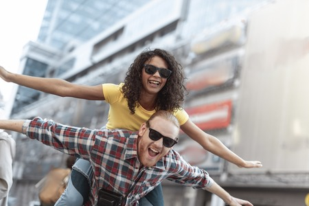 Jolly young woman and man are having fun in city Imagens