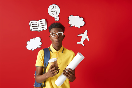 Afro American student in yellow t-shirt staying with backpack
