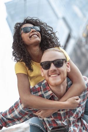 Joyful bearded guy is carrying beloved woman on back outdoors Imagens