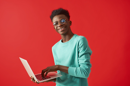 Young African American man using laptop and smiling