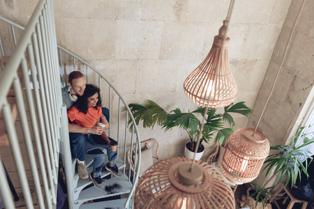 Happy man and woman are relaxing with coffee on stairwell Imagens