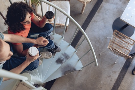 Romantic couple is drinking coffee at staircase in cafe Imagens