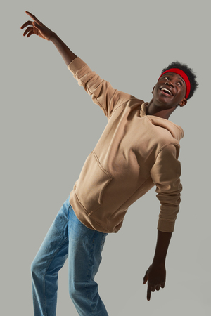 Smiling young man in beige hoodie is making dance moves