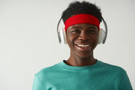 Lächelnder Afroamerikaner benutzt Kopfhörer Standard-Bild