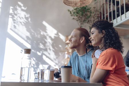 Jolly girl is having fun with beloved man in cafe Stock Photo