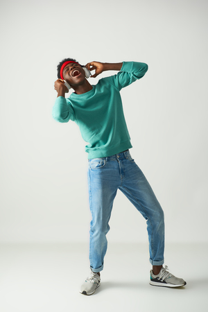 Happy young guy with red bandage is dancing in studio Stock Photo