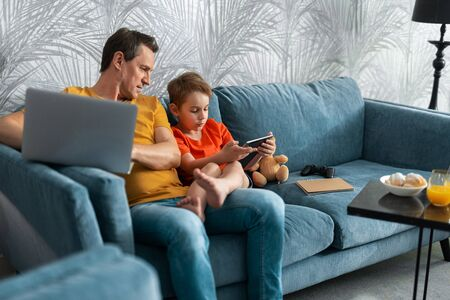 Happy dad and little son using gadgets on sofa