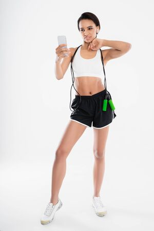 Sportive lady making selfie with jumping rope