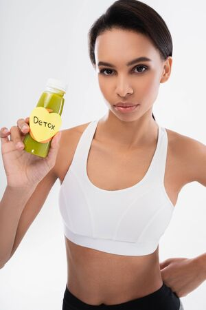 Lady holding smoothie drink with detox title