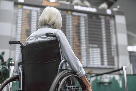 Elderly woman on wheelchair looking on flight schedule Stock Photo - 124908214