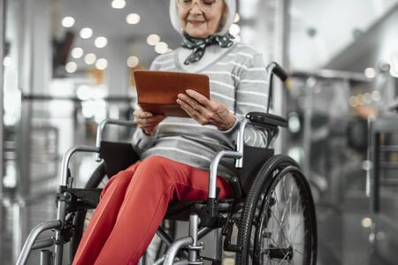 Old woman on disabled carriage with ticket at airport