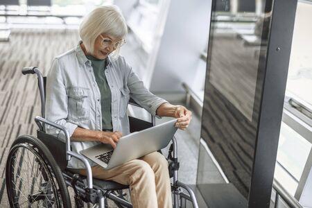 Lächelnde reife Dame auf einem behinderten Wagen, der am Laptop arbeitet