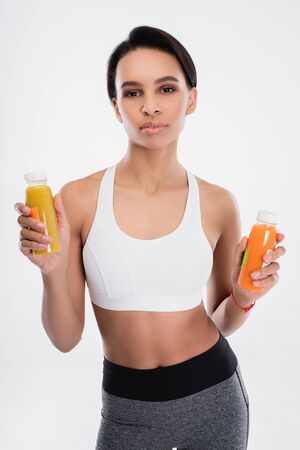 Young fitness lady holding two smoothie drinks