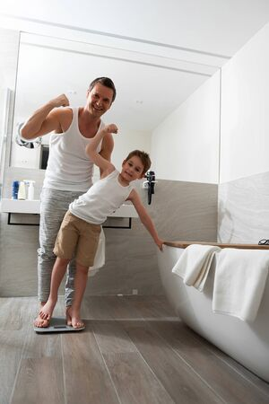 Happy father and little son measuring weight at bathroom