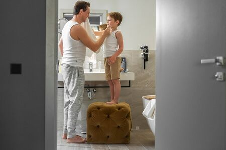Father and little son are standing in the bathroom Imagens