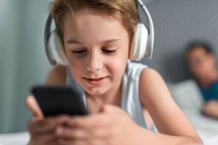 Smiling boy in headphones listening to music at home
