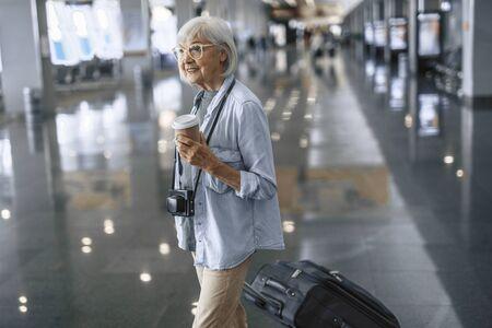 Stylish senior lady walking with camera at airport